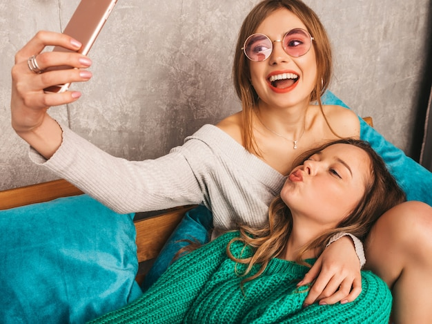 Dos jóvenes hermosas sonrientes hermosas chicas en ropa de moda de verano. mujeres despreocupadas sexy posando en el interior y tomando selfie. modelos positivos divirtiéndose con el teléfono inteligente.