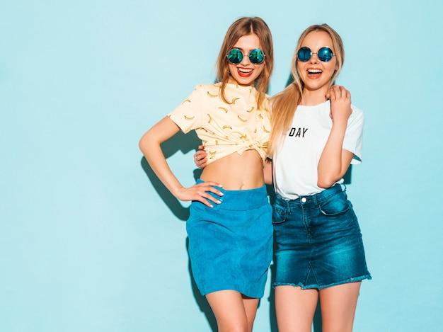 Dos jóvenes hermosas sonrientes rubias hipster chicas en jeans moda verano faldas ropa.