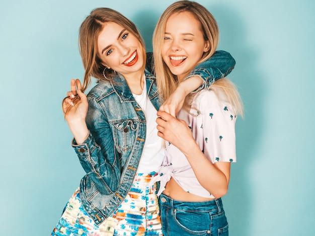 Dos jóvenes hermosas sonrientes rubias hipster chicas en ropa colorida moda verano.