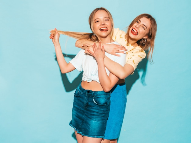 Dos jóvenes hermosas sonrientes rubias hipster chicas en ropa de verano colorida camiseta. mujeres despreocupadas sexy posando junto a la pared azul. modelos positivos divirtiéndose y mostrando la lengua
