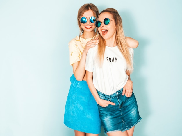 Dos jóvenes hermosas sonrientes rubias hipster chicas en ropa de verano colorida camiseta.