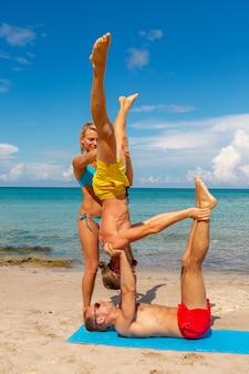Dos jóvenes hombre y mujer en la playa haciendo ejercicio de yoga fitness juntos. elemento acroyoga para fuerza y equilibrio.