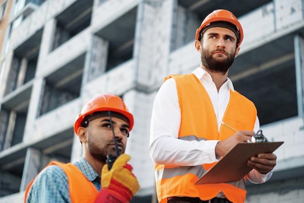 Dos jóvenes ingenieros masculinos en uniforme y cascos que trabajan en el sitio de construcción