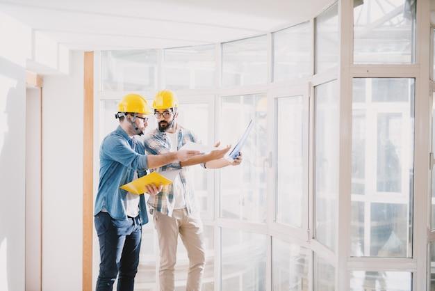 Dos jóvenes ingenieros profesionales concentrados con cascos que tienen una discusión sobre el proyecto en la hermosa y luminosa oficina con grandes ventanales.