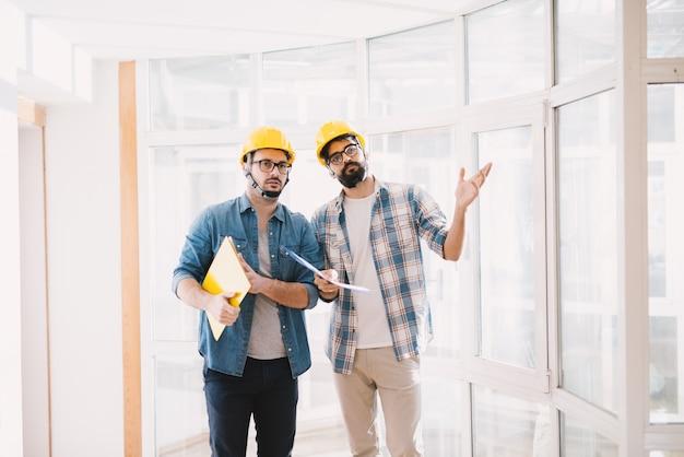 Dos jóvenes ingenieros profesionales enfocados con cascos que buscan cómo resolver un problema en la planificación de proyectos.