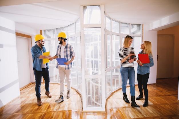 Dos jóvenes ingenieros profesionales satisfechos con cascos dándose la mano después de hacer un trato sobre el proyecto, mientras que en el lado derecho dos mujeres de negocios sonrientes sosteniendo carpetas y hablando.