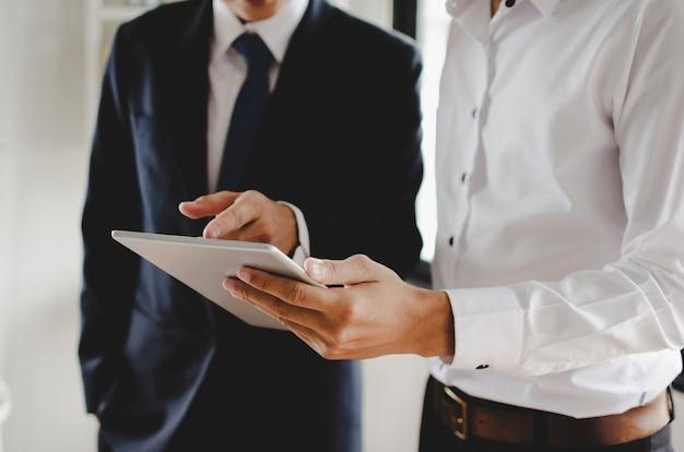 Dos jóvenes inversionistas en traje que hablan y leen información sobre noticias financieras