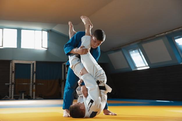 Dos jóvenes luchadores de judo en kimono entrenamiento de artes marciales en el gimnasio.