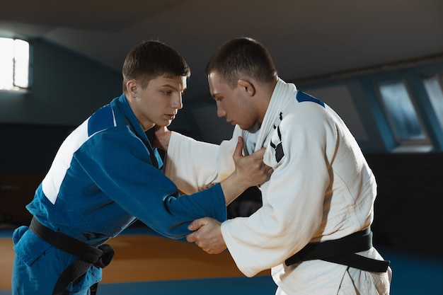 Dos jóvenes luchadores de judo en kimono entrenando artes marciales en el gimnasio con expresión en acción y movimiento