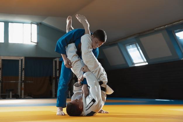 Dos jóvenes luchadores en kimono entrenando artes marciales en el gimnasio