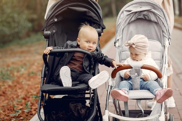 Dos jóvenes madres caminando en un parque de otoño con carruajes