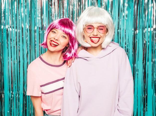 Dos jóvenes muchachas sonrientes sexy hipster en pelucas blancas y labios rojos. hermosas mujeres de moda en ropa de verano