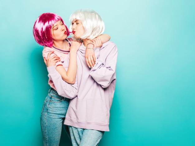 Dos jóvenes muchachas sonrientes sexy hipster en pelucas y labios rojos. hermosas mujeres de moda en ropa de verano. modelos despreocupados posando junto a la pared azul en el estudio se dan un beso al aire