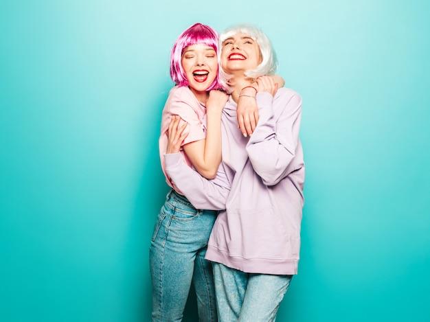 Dos jóvenes muchachas sonrientes sexy hipster en pelucas y labios rojos. hermosas mujeres de moda en ropa de verano. modelos despreocupados posando junto a la pared azul en el estudio volviéndose loco y abrazándose