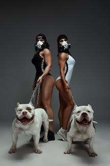 Dos jóvenes mujeres deportivas en máscara protectora mantienen perro matón americano con una correa perros