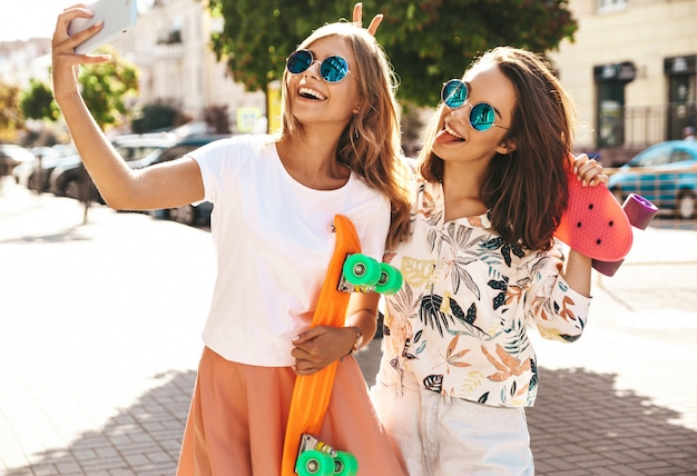 Dos jóvenes mujeres con estilo hippie morena y rubia mujeres modelos en ropa hipster de verano tomando fotos selfie para redes sociales en el teléfono. con coloridas patinetas de centavo.