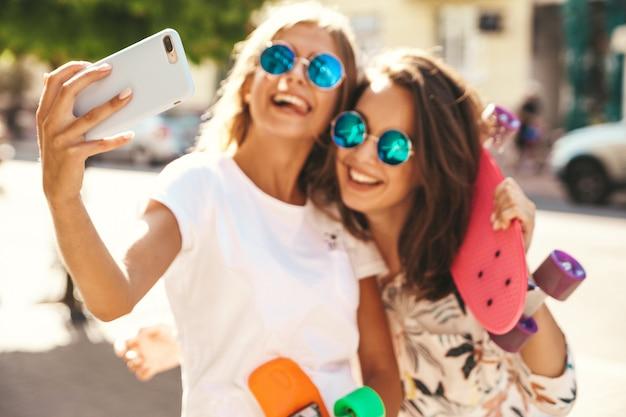 Dos jóvenes mujeres con estilo hippie morenas y mujeres rubias modelos en ropa hipster de verano tomando fotos selfie para redes sociales en teléfonos inteligentes