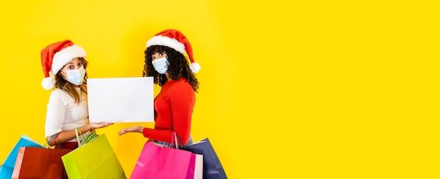 Dos jóvenes mujeres lindas con sombrero de santa claus y máscara médica, sosteniendo un cartel para copiar el espacio con muchas bolsas de la compra - banner de navidad