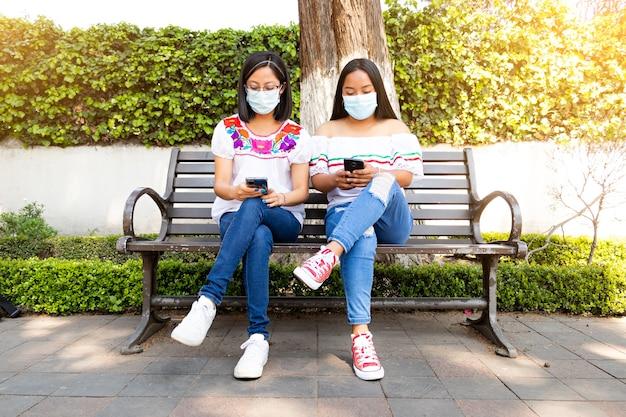 Dos jóvenes mujeres mexicanas sentadas en un banco con sus teléfonos celulares en la calle con máscaras