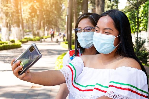 Dos jóvenes mujeres mexicanas, sentadas en un banco tomando un selfie en una calle arbolada, con máscaras