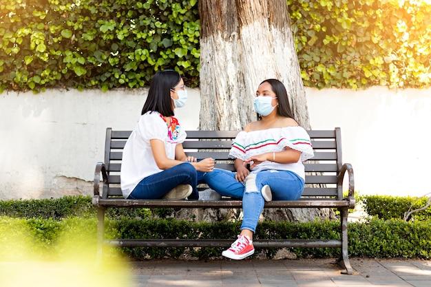 Dos jóvenes mujeres mexicanas, sentados en un banco en una calle arbolada en un día soleado, con máscaras