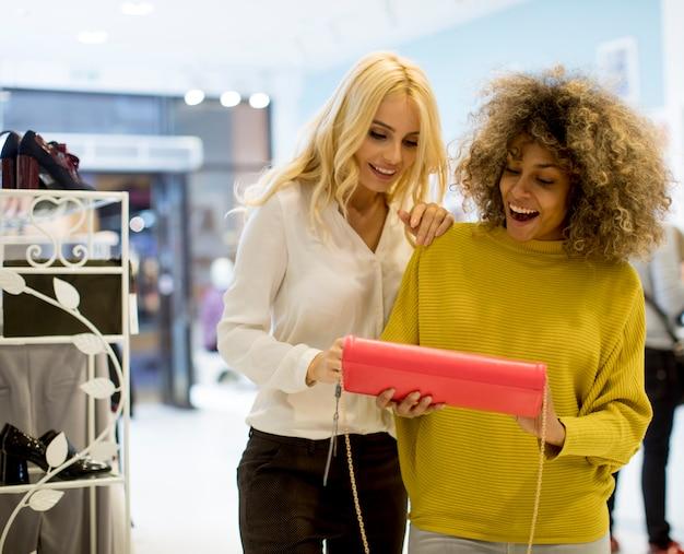 Dos jóvenes mujeres multiétnicas compran monedero en la tienda