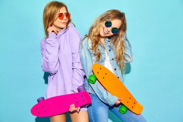Dos jóvenes mujeres rubias sonrientes con estilo con patinetas centavo. mujeres en ropa deportiva de verano hipster posando junto a la pared azul. modelos positivos