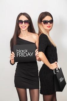 Dos jóvenes mujeres sonrientes mostrando bolsa de compras en viernes negro de vacaciones