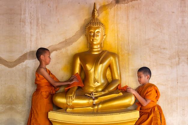 Dos jóvenes novicios monje fregar la estatua de buda en el templo en tailandia