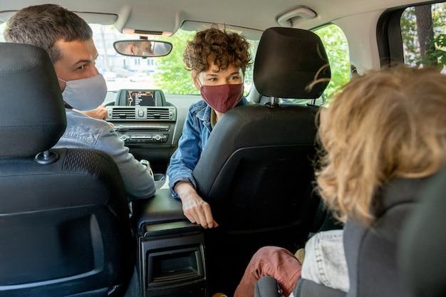 Dos jóvenes padres contemporáneos con máscaras protectoras y ropa informal mirando a su pequeño hijo en el asiento trasero y hablando con él
