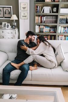 Dos jóvenes pareja sentada en el sofá haciendo el amor en la casa moderna