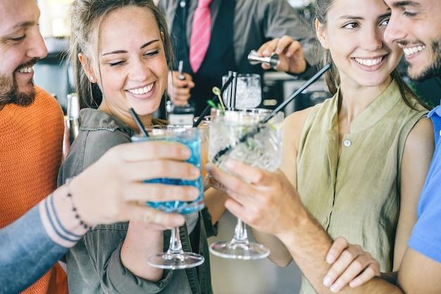 Dos jóvenes parejas enamoradas brindis de cócteles en un bar
