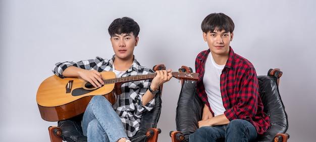 Dos jóvenes se sentaron en una silla y tocaron la guitarra.