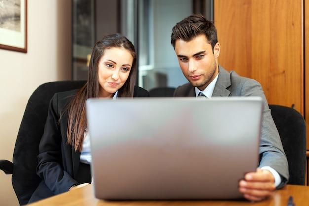 Dos jóvenes socios comerciales discutiendo planes o ideas en una reunión