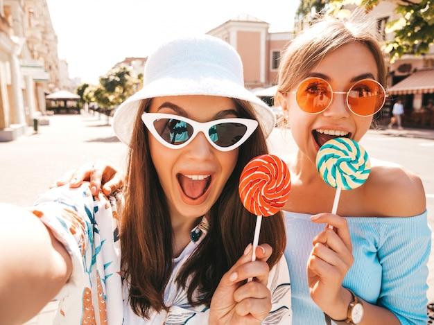 Dos jóvenes sonrientes mujeres hipster en ropa casual de verano.