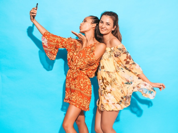 Dos jóvenes sonrientes mujeres hipster en vestidos de verano hippie. chicas tomando fotos de autorretrato en smartphone. modelos posando junto a la pared azul en el estudio. la mujer da un beso al aire
