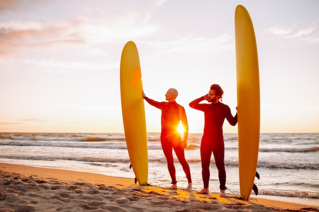 Dos jóvenes surfistas en traje negro con longboards de surf amarillo en una costa del océano al atardecer océano. campamento de aventura de deportes acuáticos y baño extremo en vacaciones de verano.