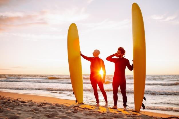 Dos jóvenes surfistas en traje negro con longboards de surf amarillos en una costa del océano al atardecer océano