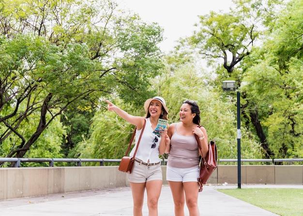 Dos jóvenes turistas mujeres caminando en el parque mirando a otro lado