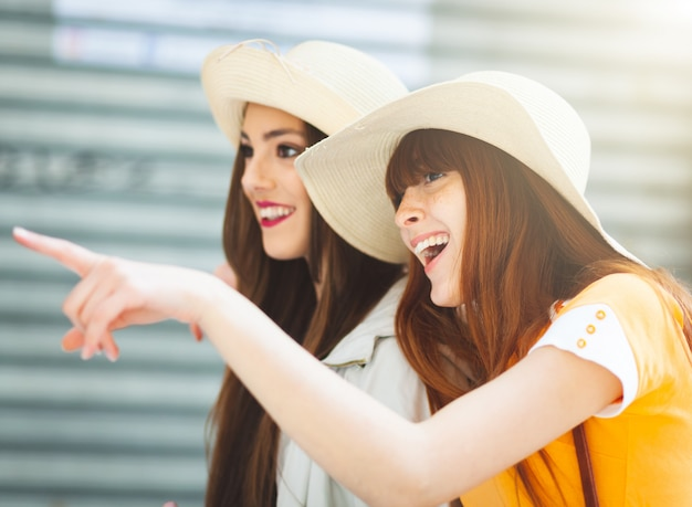 Dos jóvenes turistas con sombreros de paja.