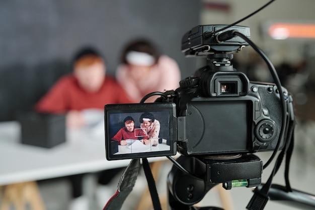 Dos jóvenes vloggers masculinos contemporáneos en la pantalla de la cámara de vídeo de pie delante del escritorio en el estudio