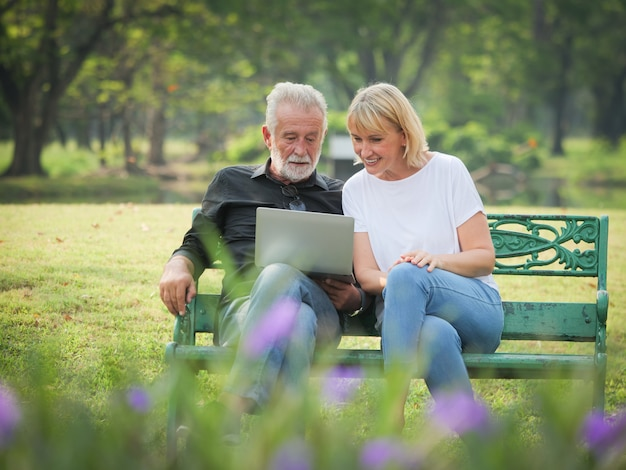 Dos jubilaciones de personas mayores felices el hombre y la mujer están sentados y usando una computadora portátil en el parque