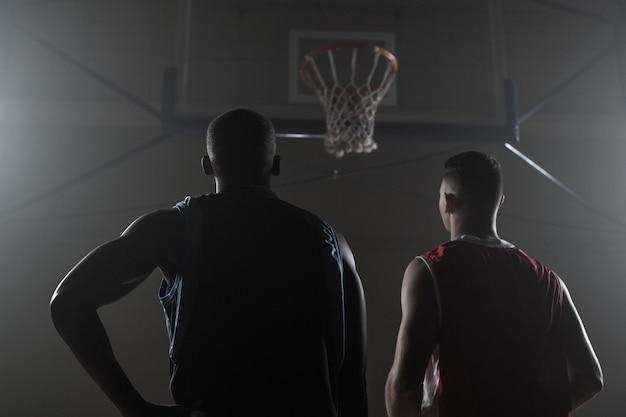 Dos jugadores de baloncesto mirando el aro de baloncesto