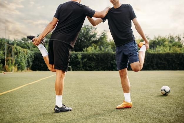 Dos jugadores de fútbol haciendo ejercicio de estiramiento en el campo. entrenamiento de fútbol en el estadio al aire libre, entrenamiento del equipo antes del juego