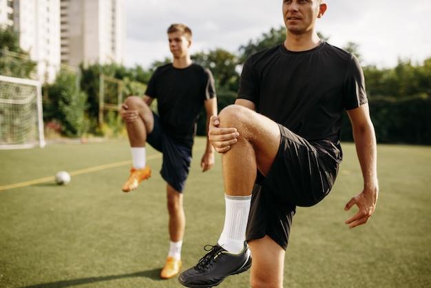 Dos jugadores de fútbol masculino haciendo ejercicio de estiramiento en el campo. entrenamiento de fútbol en el estadio al aire libre, entrenamiento antes del juego