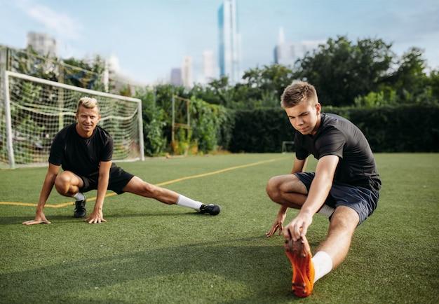 Dos jugadores de fútbol masculino haciendo ejercicio de estiramiento en el campo. entrenamiento de fútbol en el estadio al aire libre, entrenamiento del equipo antes del juego