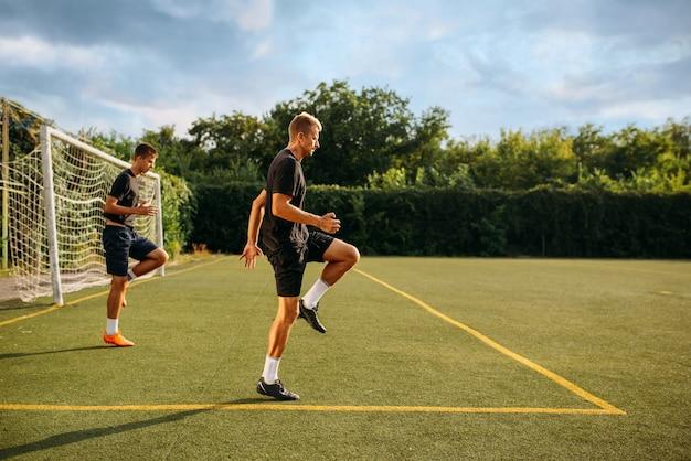 Dos jugadores de fútbol masculinos entrenando en el campo. futbolistas en el estadio al aire libre, entrenamiento del equipo antes del juego
