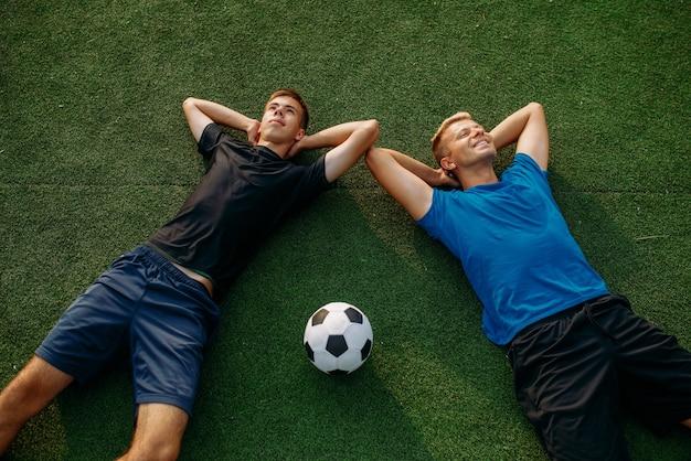 Dos jugadores de fútbol masculinos recostados sobre la hierba en el campo, vista superior. futbolista en el estadio al aire libre, entrenamiento antes del juego, entrenamiento de fútbol