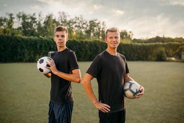 Dos jugadores de fútbol masculinos sosteniendo pelotas en las manos en el campo. futbolista en el estadio al aire libre, entrenamiento antes del juego, entrenamiento de fútbol