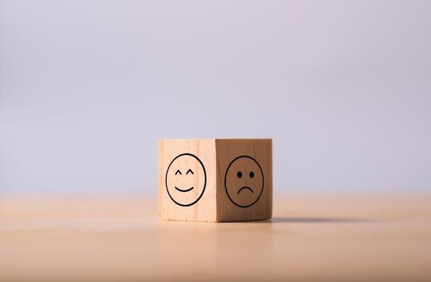 Dos lados opuestos de emoción de feliz y triste que imprimen la pantalla en madera cúbica. encuesta de experiencia del cliente y concepto de comentarios de satisfacción.